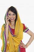 stock photo of dupatta  - Beautiful Indian woman in traditional wear answering phone call over gray background - JPG