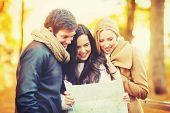 holidays and tourism concept - group of friends with tourist map in autumn park