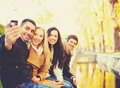holidays, vacation, travel and tourism concept - group of friends or couples having fun in autumn pa