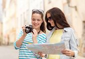 tourism, travel, leisure, holidays and friendship concept - two smiling teenage girls with map and c