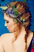 portrait of a beautiful woman with red hair in curly braided hairstyle wearing a crown of fresh flow