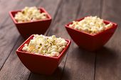 foto of popcorn  - Three red bowls of freshly prepared salted popcorn  - JPG