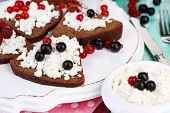 Bread with cottage cheese and berries on wooden tray close-up