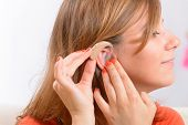 stock photo of deaf  - Putting on a deaf aid - JPG