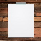 Empty white paper sheet stick on wood texture background.