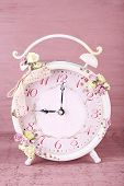 Beautiful vintage alarm clock with flowers on pink wooden background