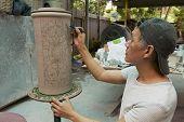 Man paints traditional tribal tattoo motives decoration, Kuching, Malaysia.
