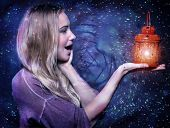 Closeup portrait of cute blond girl with surprise looking on red glowing lantern in hand over dark starry night, Christmas magic concept