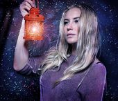 Closeup portrait of beautiful woman with glowing lantern in hands over starry sky, magical Christmas night, fashion concept