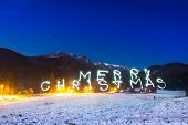 Merry Christmas sign under Tatra mountains at night, Poland