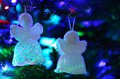 stock photo of christmas angel  - Knitted Christmas angels on Christmas lights background - JPG