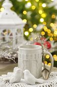 Mug with hot drink and Christmas decorations on fir tree background