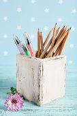 Different pens and pencils near flower on color wooden table on color wooden table and blue background with printed stars