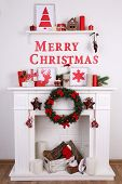 Fireplace with Christmas decoration on wooden floor and white wall background
