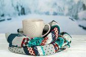 Cup of hot drink with warm scarf on table