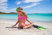 foto of flipper  - Little girl with flippers and goggles for swimming on the beach - JPG