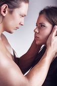 image of foreplay  - Young beautiful loving couple is embracingon a gray background - JPG