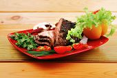 beef on red plate with vegetables over wood