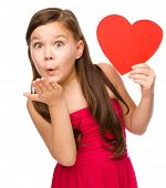 Little girl is holding red heart and blowing a kiss, isolated over white