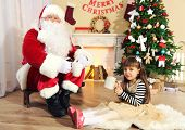 Santa Claus drinking hot chocolate with little cute girl near Christmas tree at home
