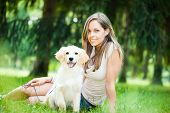 Young woman playing with her golden retriever puppy outdoors