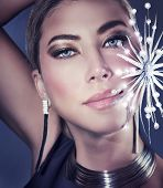 Beautiful woman portrait on dark gorgeous female with stylish shiny makeup wearing fashionable accessories and holding decorative bright snowflake