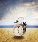 Clock on sand at beach. bright sky behind