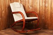 Modern rocking-chair on wooden wall background
