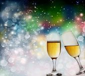 Toasting with two champagne glasses against colorful holiday lights