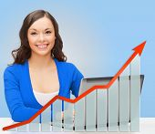 people, technology, statistic sand business concept - smiling woman in blue clothes with laptop computer over blue background and growth chart