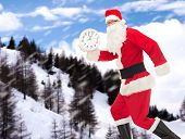 christmas, holidays and people concept - man in costume of santa claus running with clock showing twelve over snowy mountains background