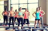 fitness, sport, training, gym and lifestyle concept - group of women working out with steppers in gym