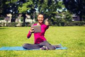 fitness, park, technology, gesture and people concept - smiling african american woman with tablet pc showing thumbs up outdoors
