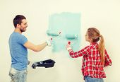 repair, building and home concept - smiling couple painting wall at home