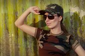Young Woman Soldier in Camouflage Outfit Saluting