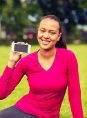 fitness, park, technology and sport concept - smiling african american woman showing smartphone outdoors