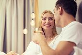 hotel, travel, relationships and happiness concept - smiling couple with champagne glasses in bed