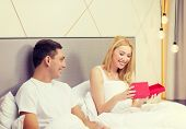 hotel, travel, relationships, holidays and happiness concept - smiling couple in bed with red gift box