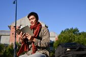 A portrait of young student holding book at campus