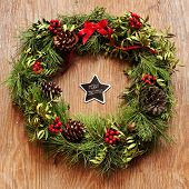 the sentence merry christmas written in a star-shaped chalkboard and a natural christmas wreath hanging on a rustic wooden door