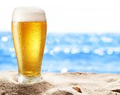 Photo of cold beer botle in the sand. Sparkling sea at the background.
