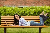 Peaceful brunette lying on bench using laptop in the park