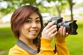 Portrait of beautiful female photographer at the park