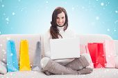 Pretty brunette using laptop on the couch against blue vignette