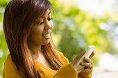 Beautiful young woman text messaging in the park