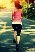 runner athlete running at road. woman fitness jogging workout wellness concept.