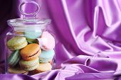 Gentle colorful macaroons in glass jar on color fabric background