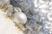 Silver Christmas background with baubles and gifts nestled in snow