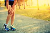 pic of pain-tree  - young woman runner sports injured leg outdoor  - JPG