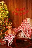 Decorated Christmas tree and rocking chair on wooden wall background